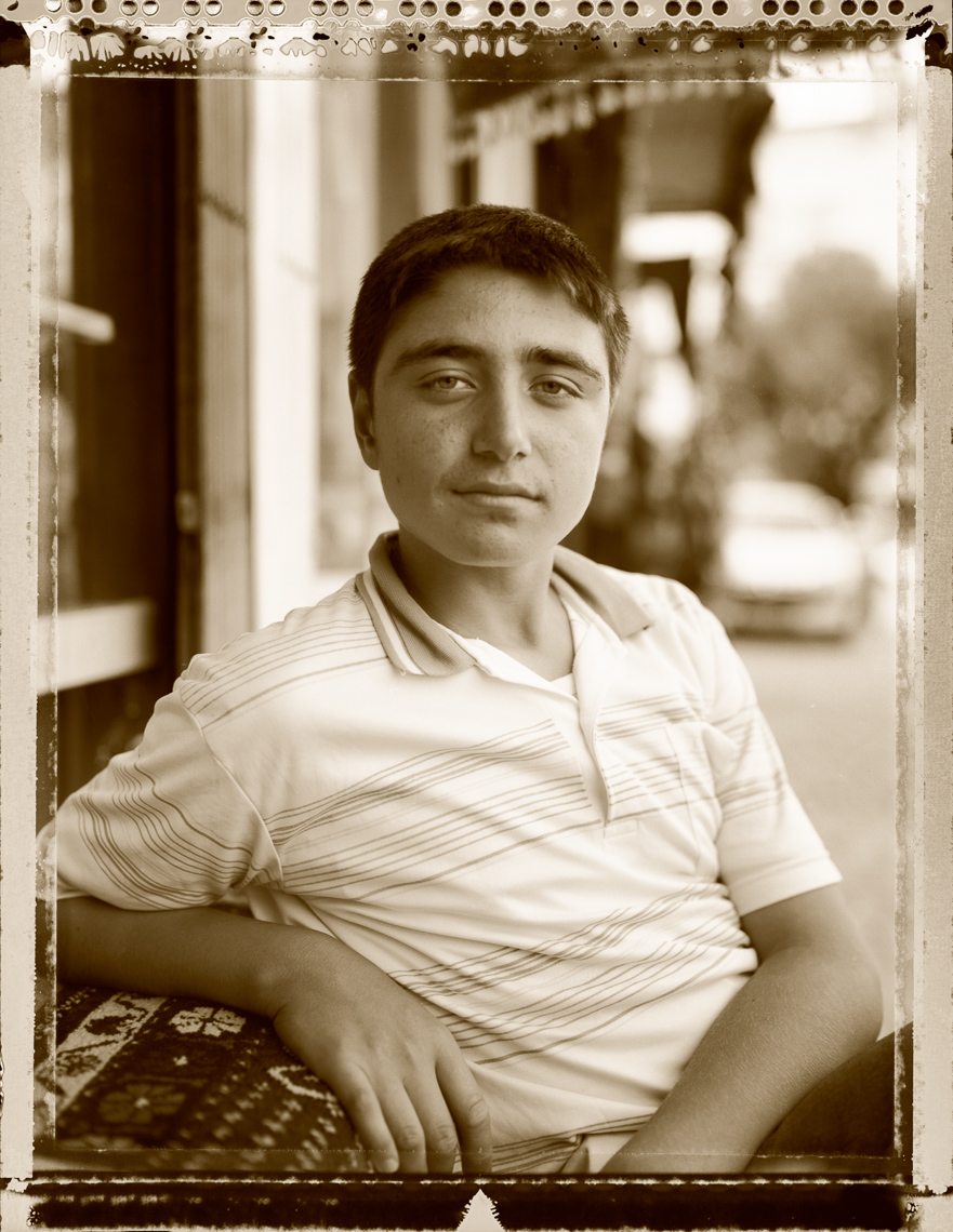 Kurdish portrait of young man at Kilim shop, Konya Turkey.