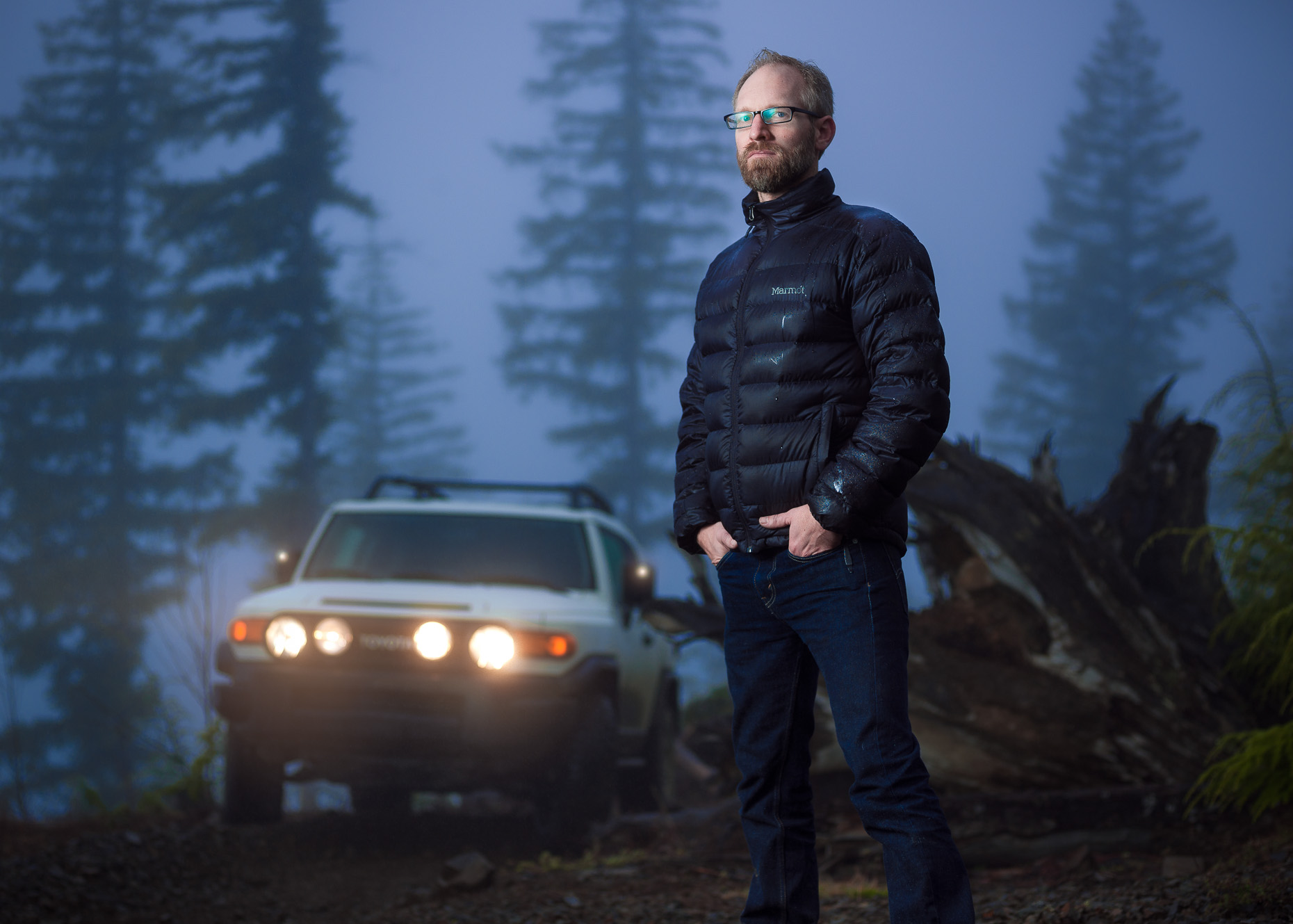 Dramatic twilight portrait in fog of guy and his SUV