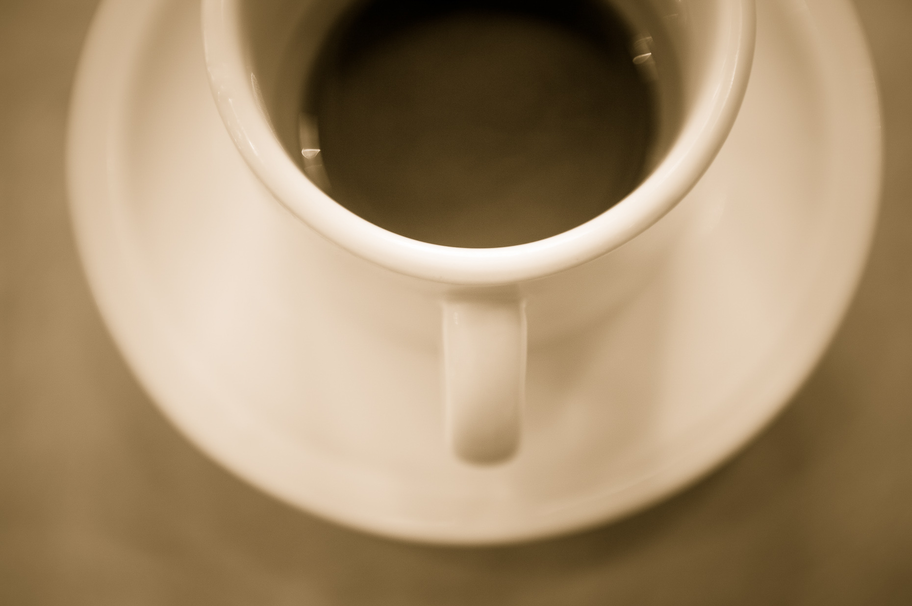 Sepia toned coffee cup and saucer shot from overhead.