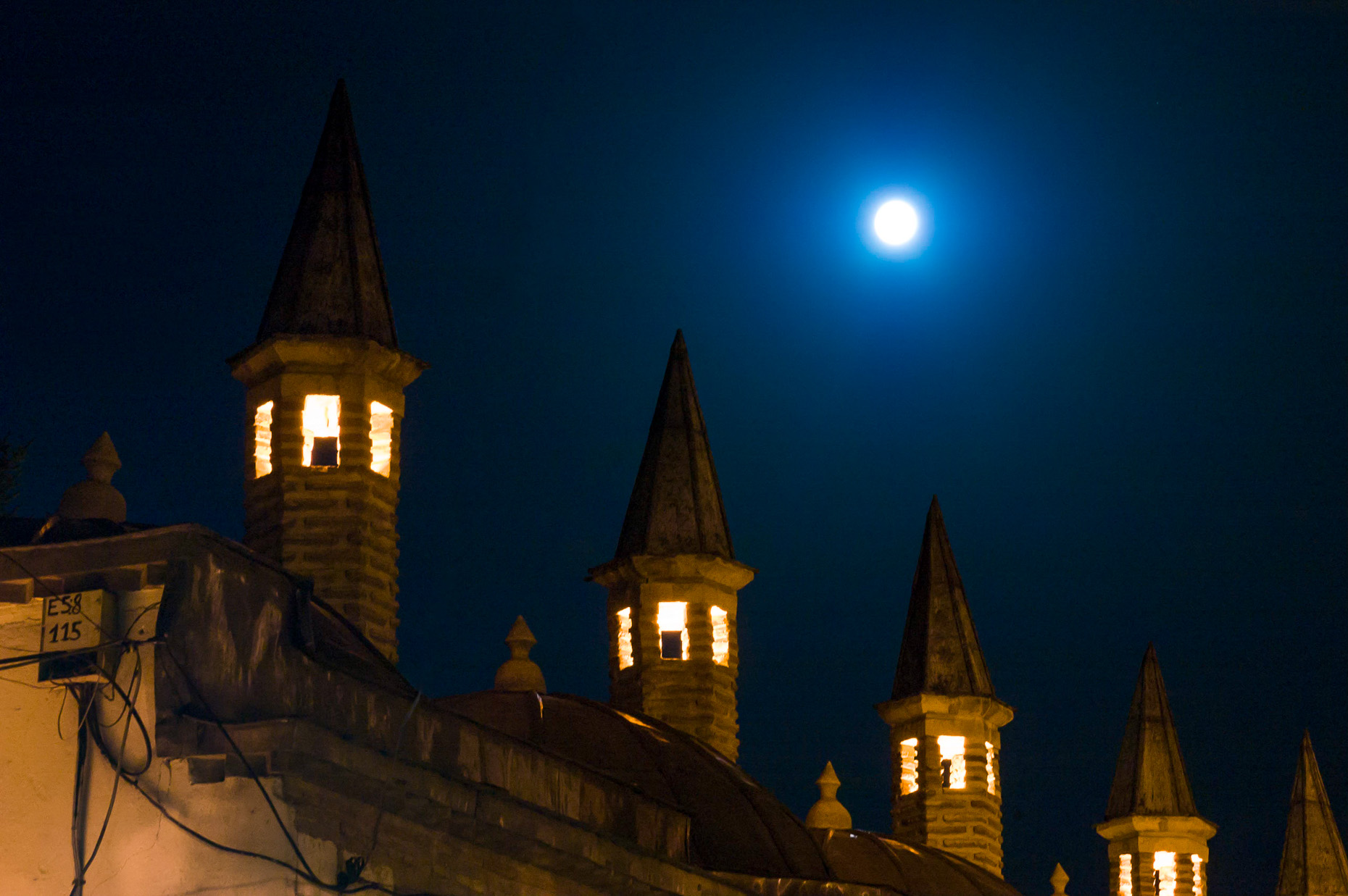 Image of spires of Mevlana Sufi Mosque at night with full moon, Konya, Turkey.