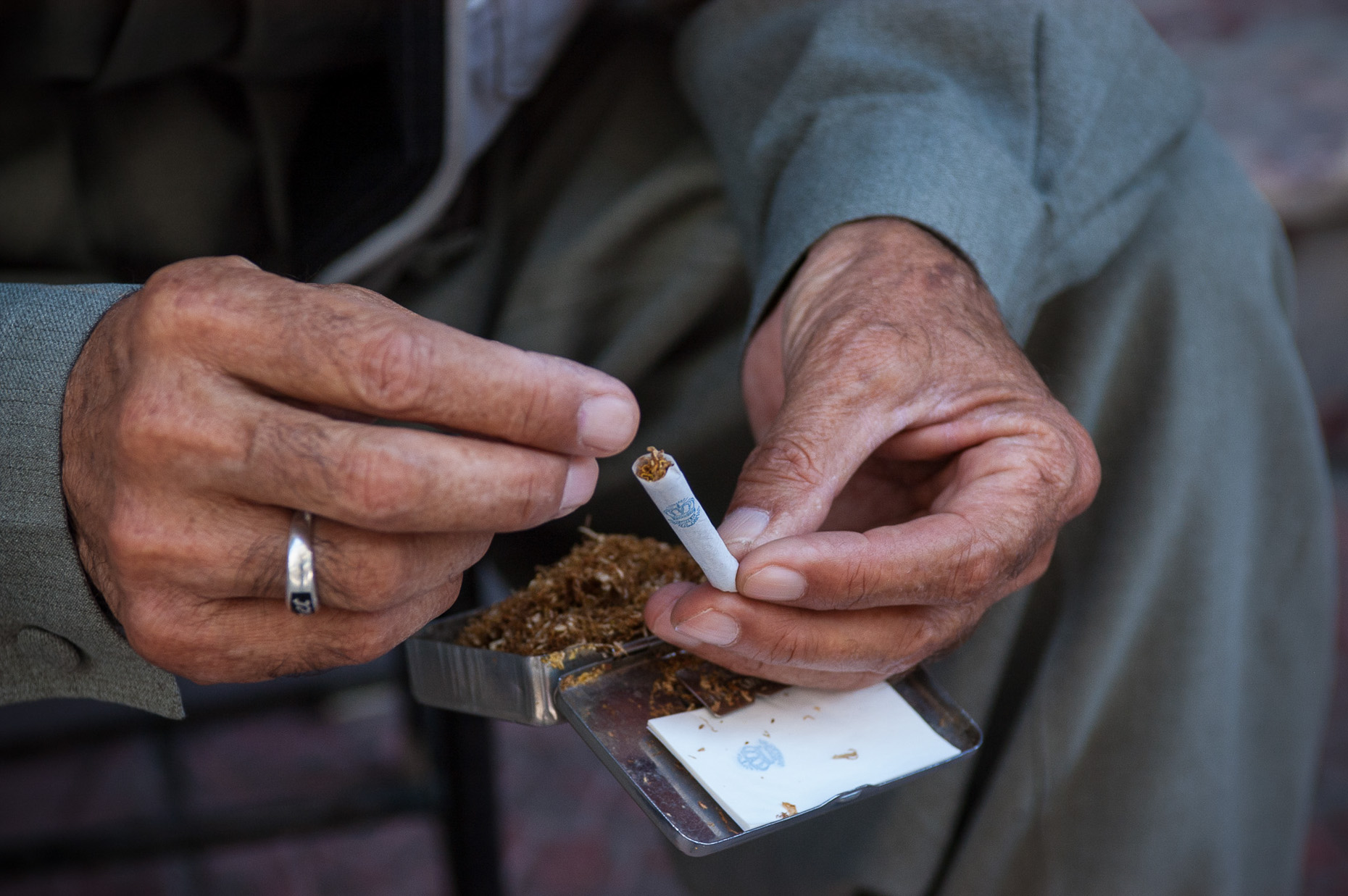 Portrait of Kurdish village elder rolling his own tobacco cigarette.