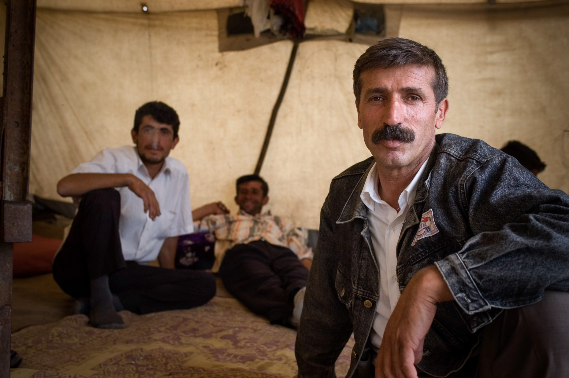 Environmental portrait of nomadic Kurdish men lounging inside yurt, in mountains near Syria Turkey.