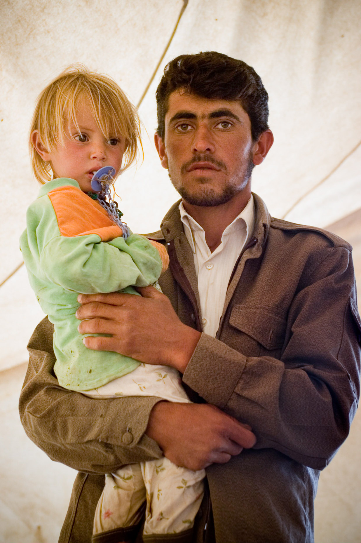 Portrait of Kurdish Peshmurga guard and his blond haired son.