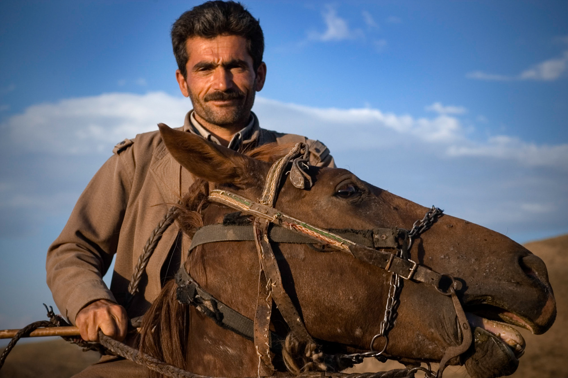 Environmental portrait of Kurdish Peshmurga guard on horseback, near mountain village, Turkey.