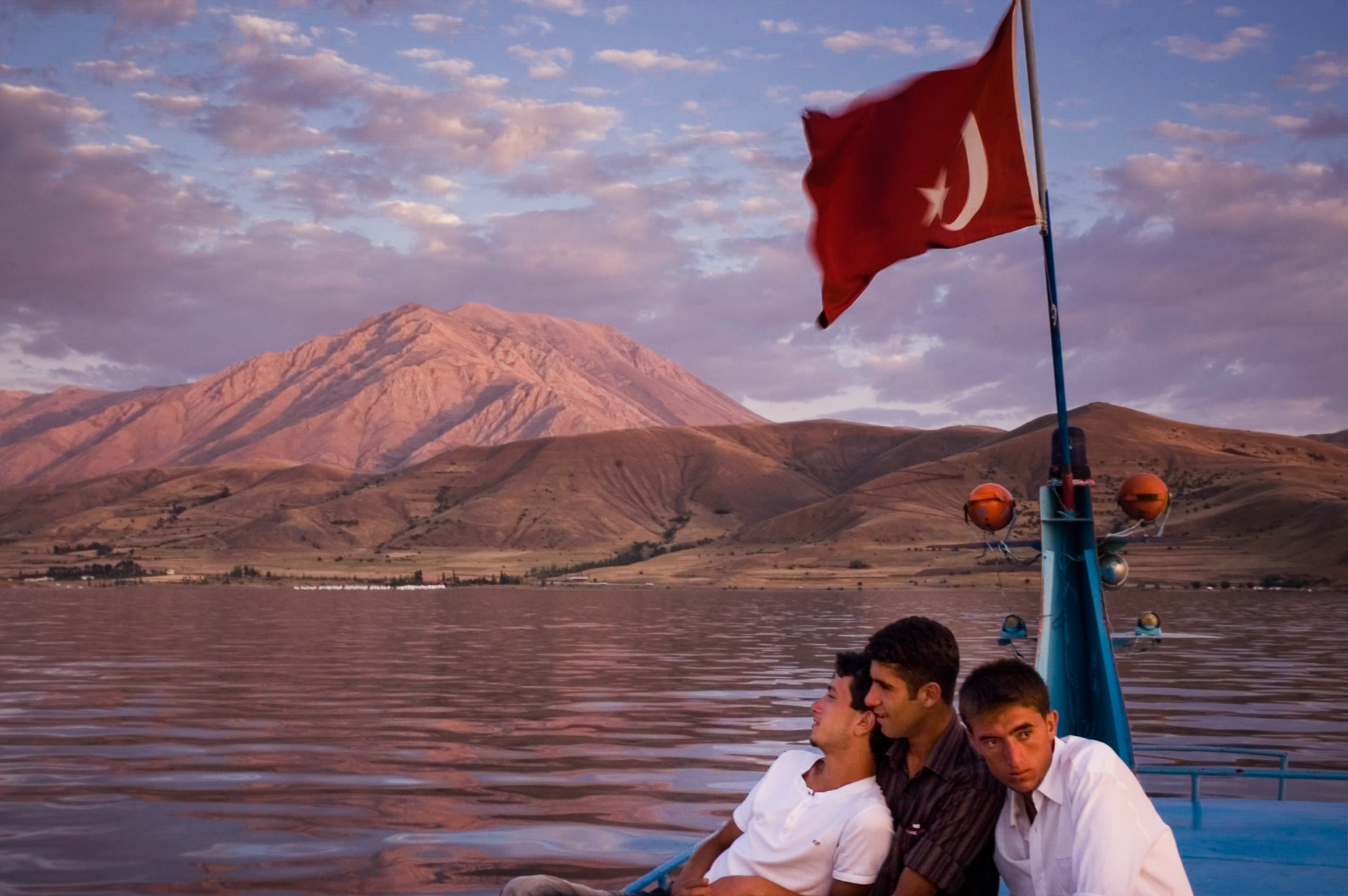Young Kurdish men on boat on Van Lake under Turkey flag, Akdamar Island Turkey.