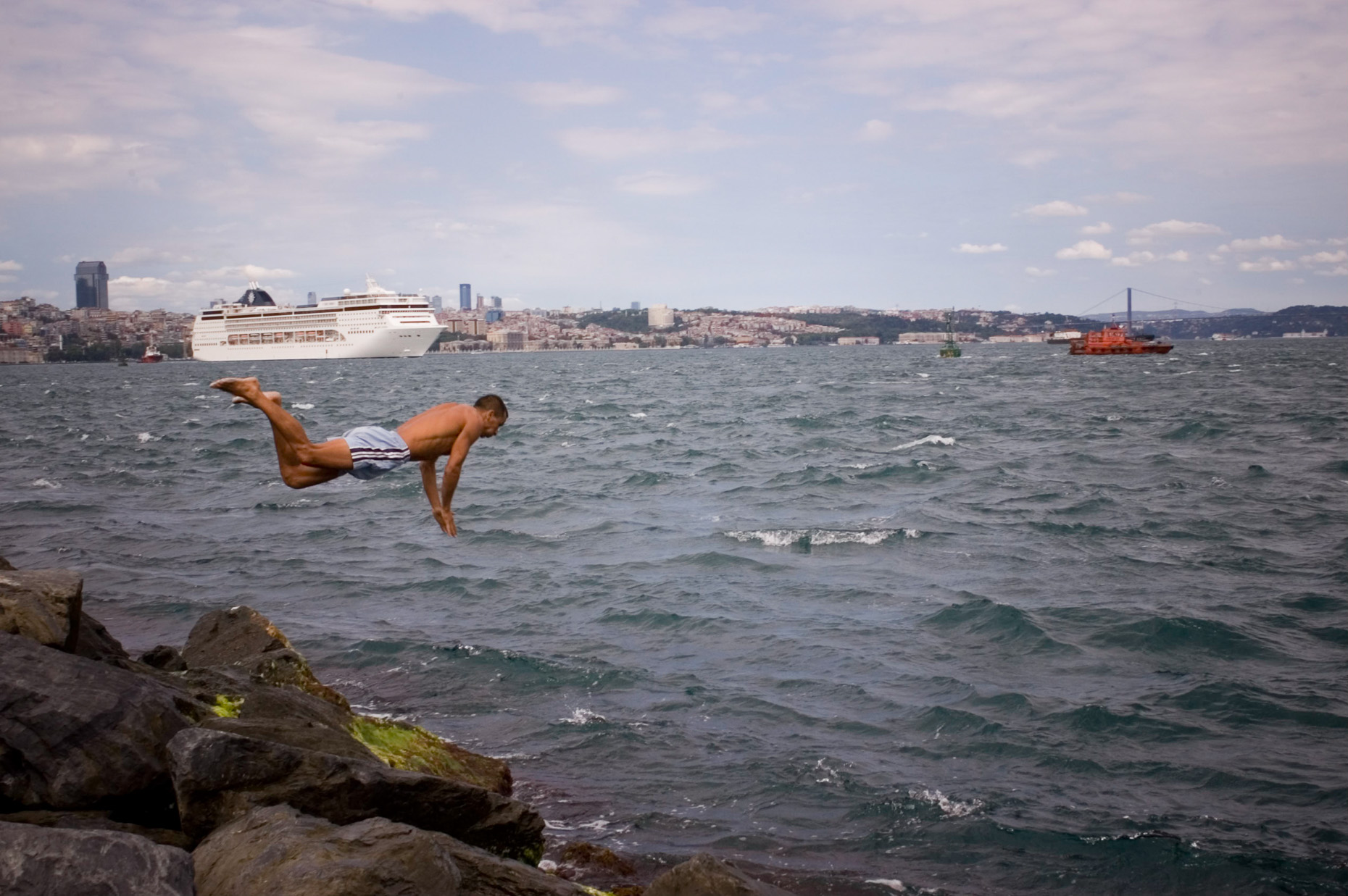 Image of man diving into the Bosporus Sea with cruise ship in background Istanbul Turkey.