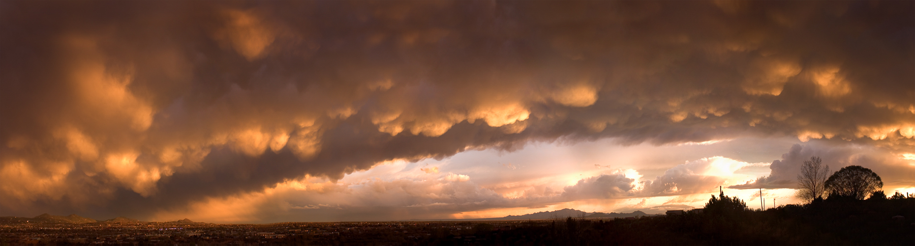 Panoramic of dramatic storm canopy of undelit clouds at sunset, Santa Fe New Mexico.