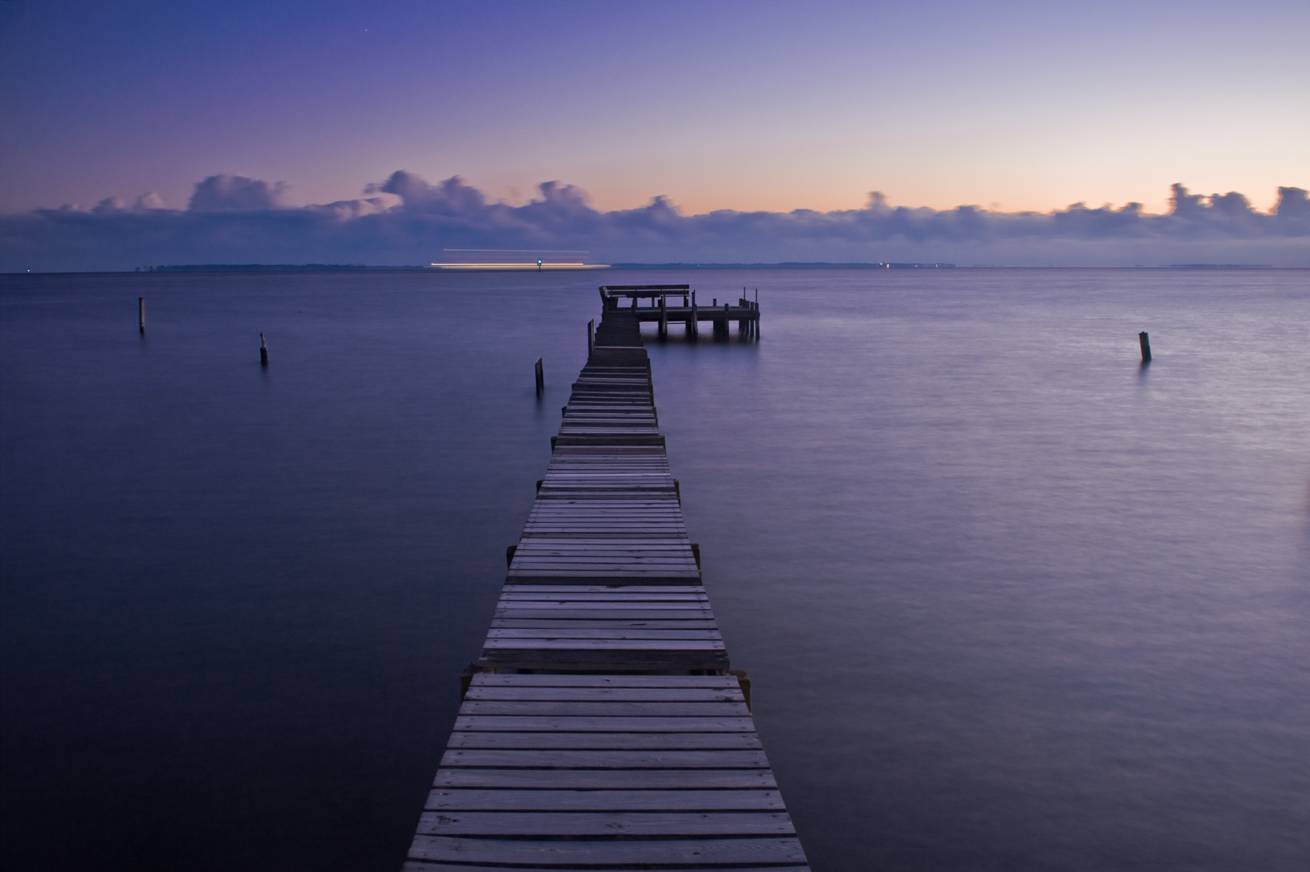 Quiet dock in water at dawn twilight, near Currituck NC.