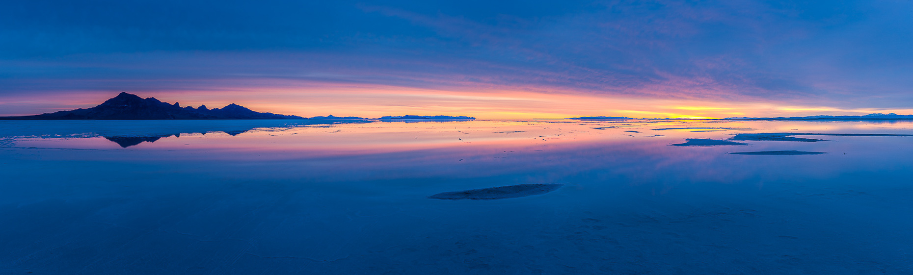 Panoramic image of dawn on Salt Lake, blue light and golden sun.  Bonneville Salt Flats, Utah.
