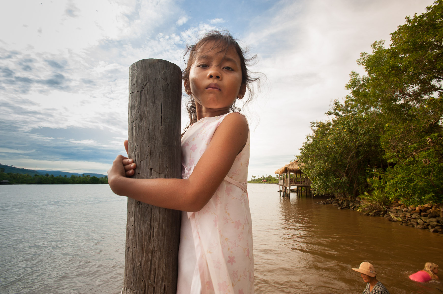 Young Cambodian girl on dock of river, Kampot, Cambodia.