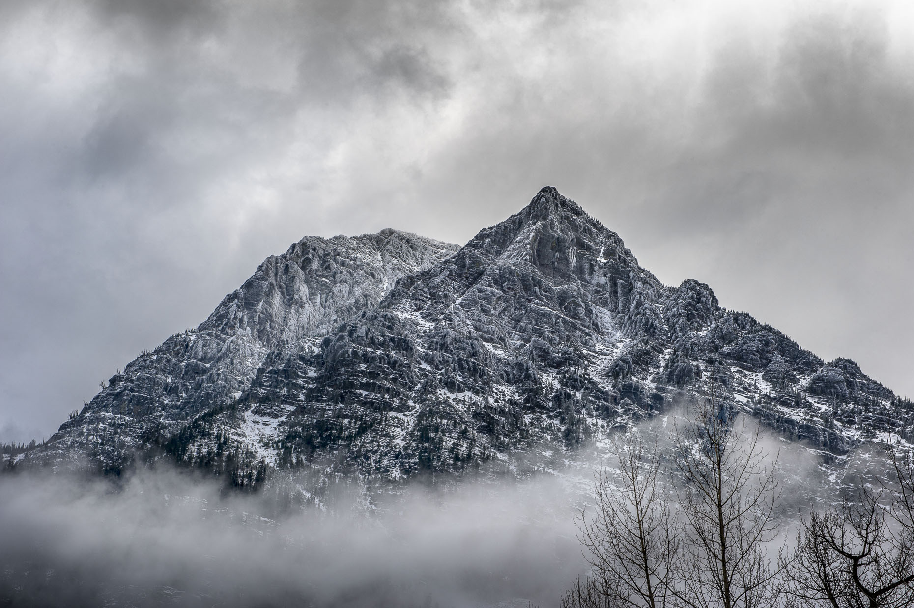 Image of granite peak in  snowy weather near mountain in Glacier National Park, WY.