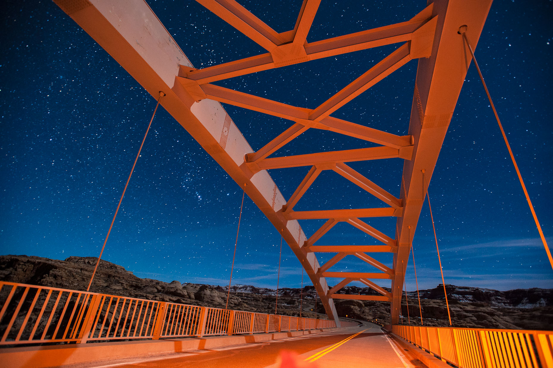 Image of bridge structure at night with star lit sky over Colorado River, Utah.
