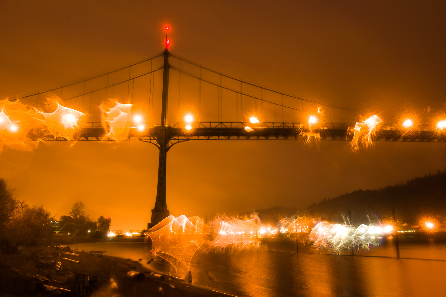Night image of St. Johns Bridge with orange bridge lights, rain drops, Oregon.