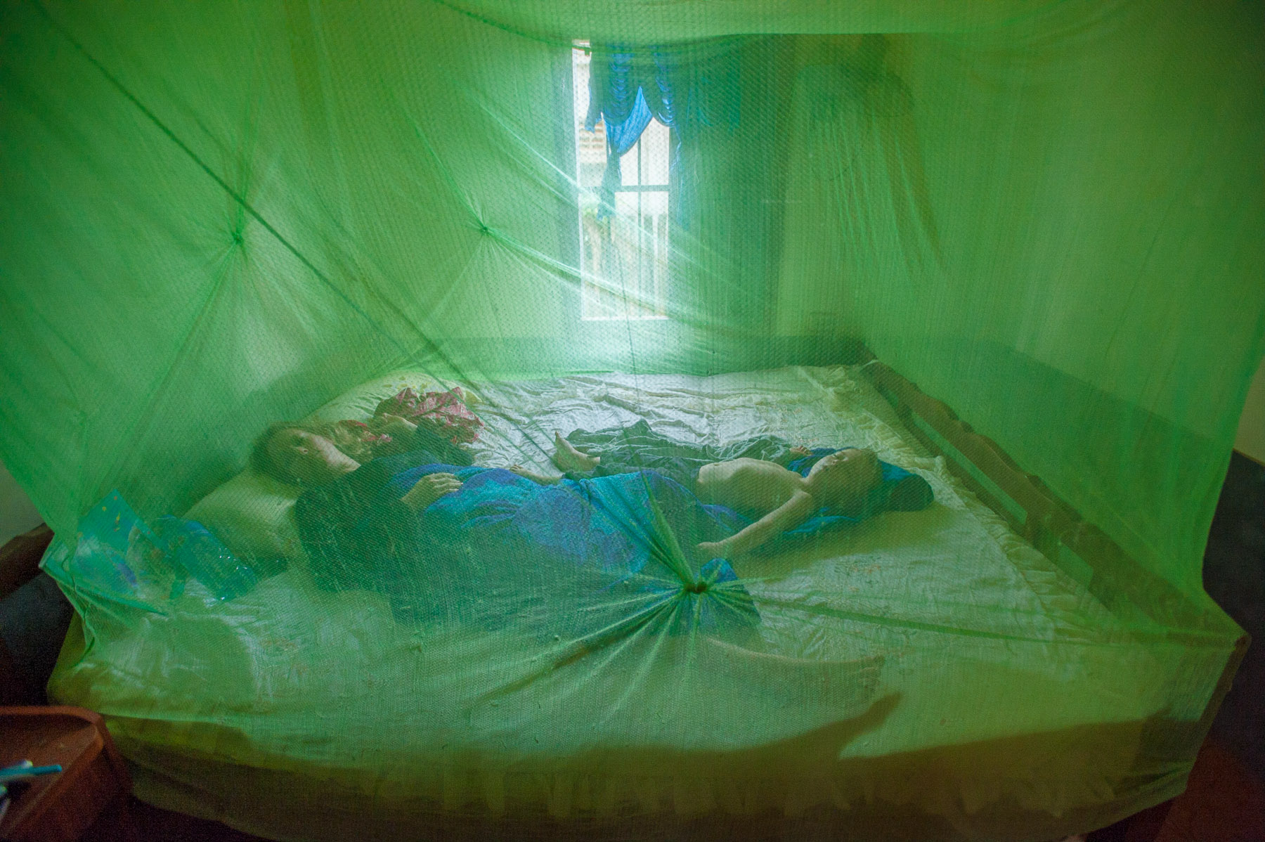Mother and son sleeping under mosquito net, remote village Cambodia.