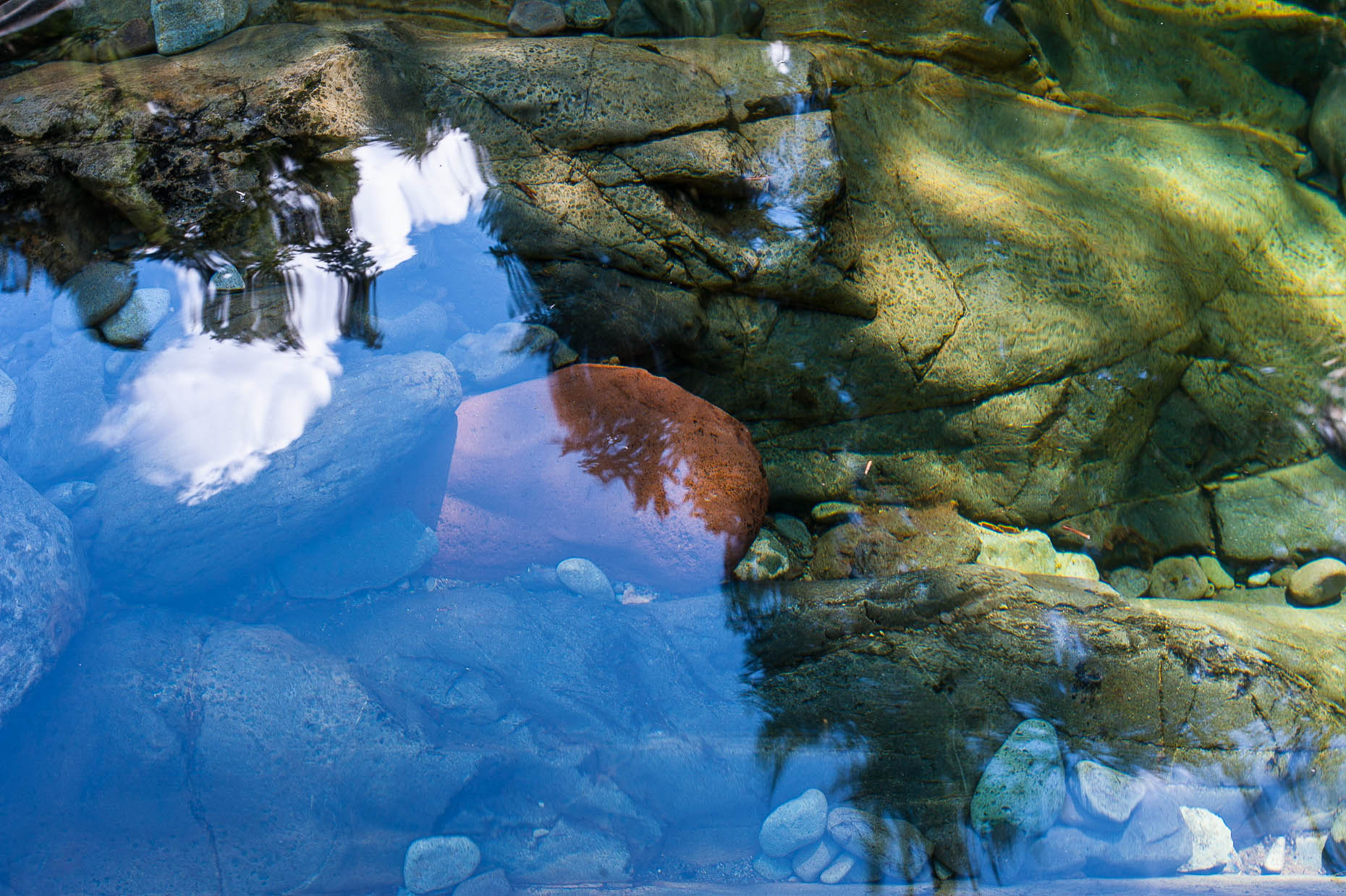 Photo of water reflection with river rocks under water.