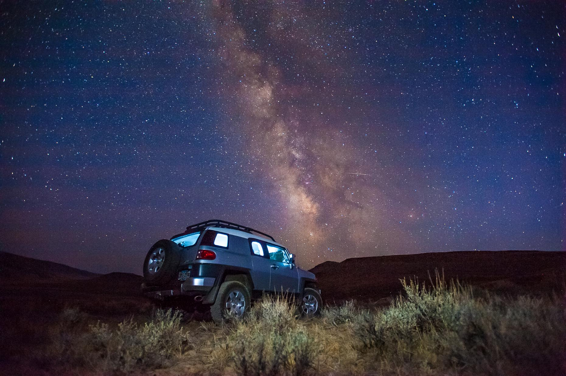 Image of Milky Way Galaxy and FJ Cruiser in desert.