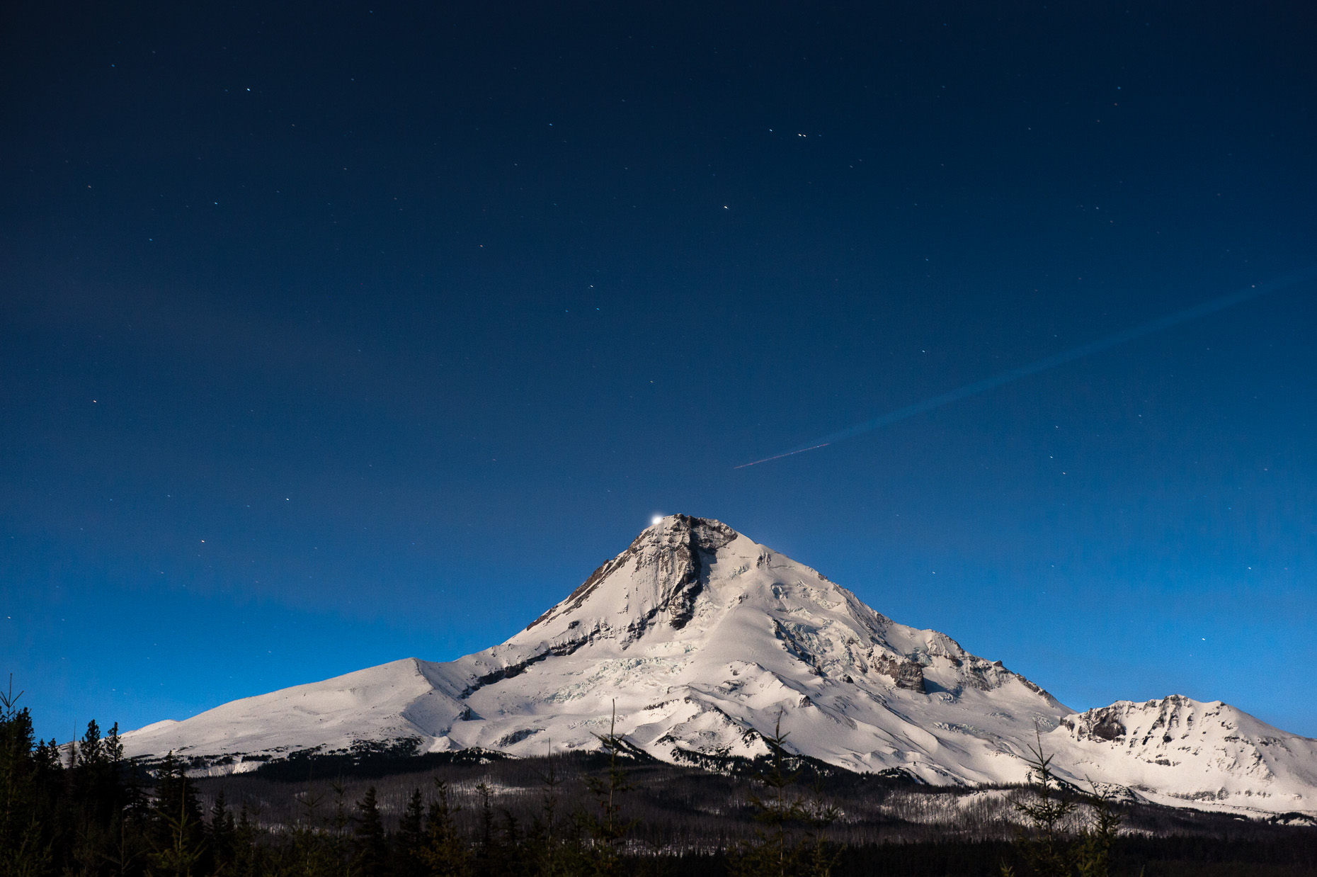 Nightime photo of Mt Hood with jet trails and backlit by Venus.