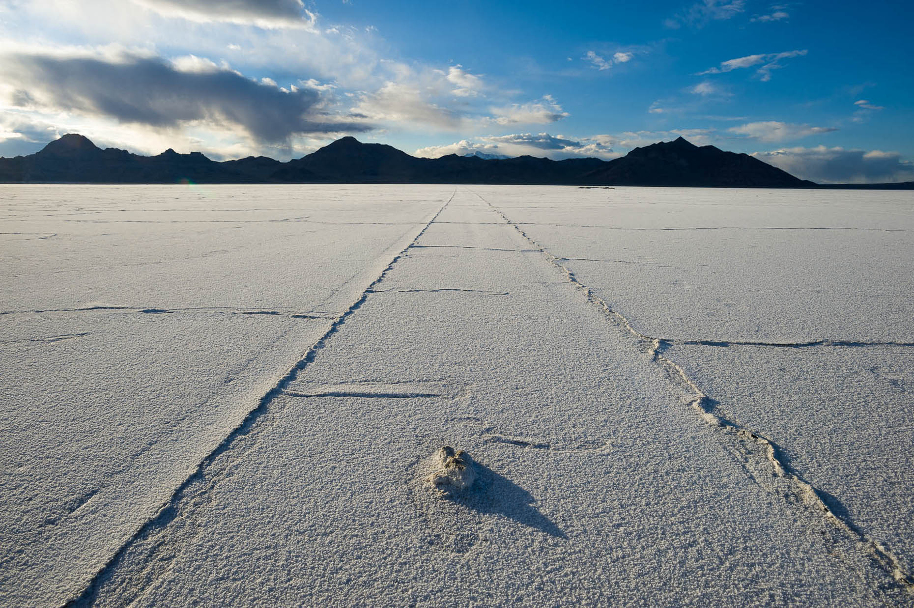 Receding tire track lines in Salt Flats, Utah with blue sky and mountains on horizon.