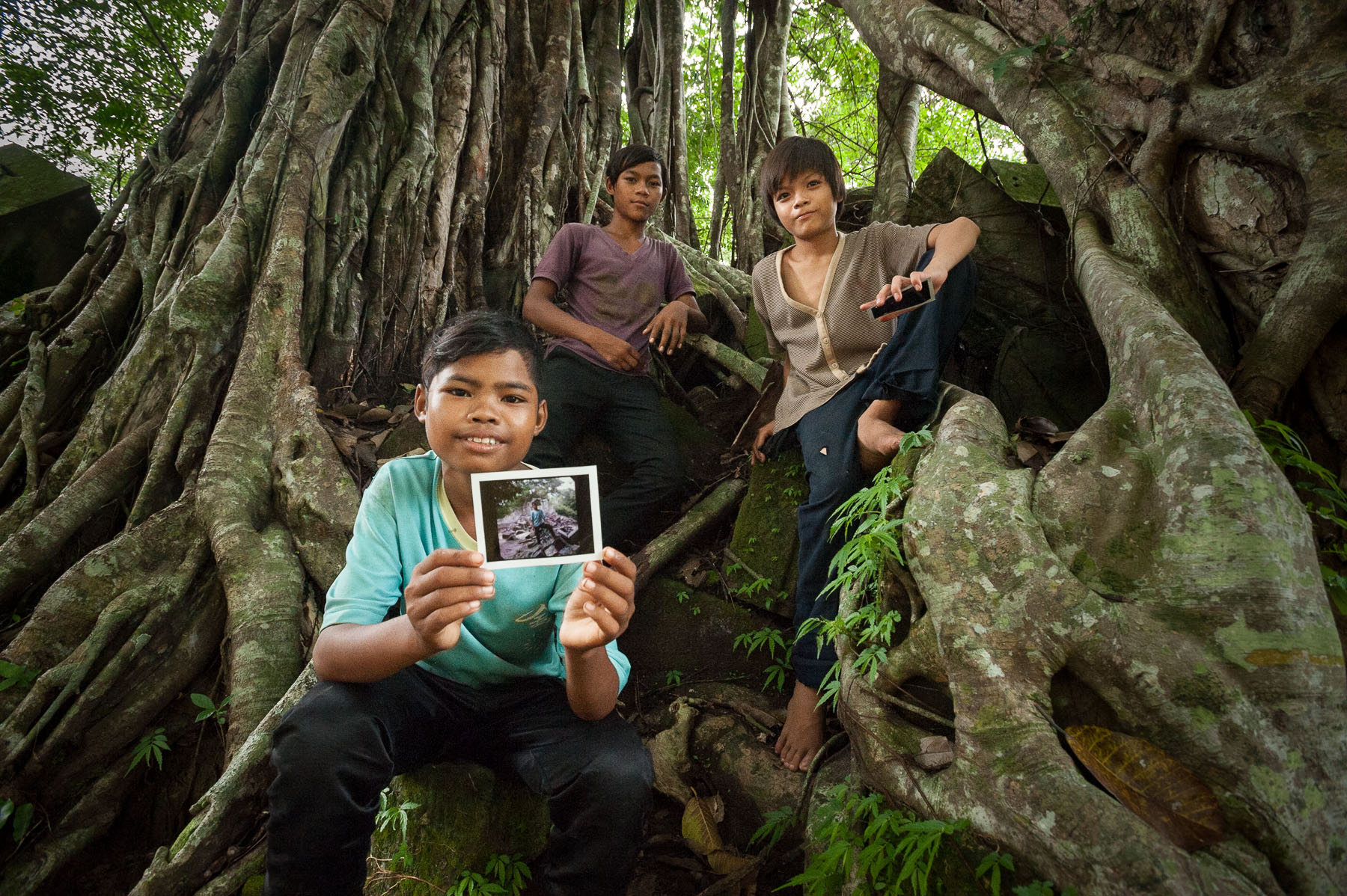 Cambodian kids with Polaroid pictures at Banteay Srey temple, Cambodia.