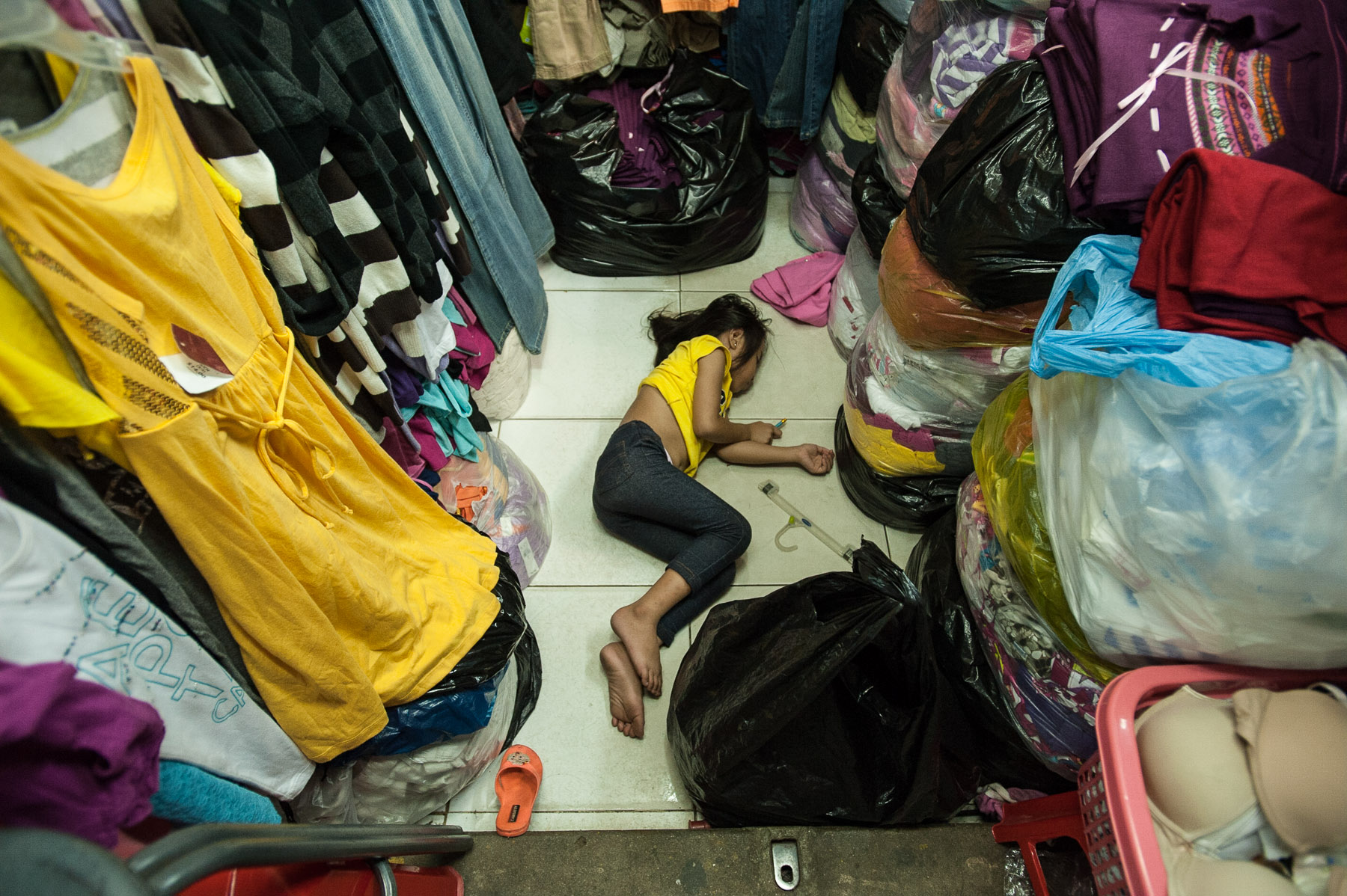 Girl asleep on floor of market stall, Russian market, Phnom Penh Cambodia.