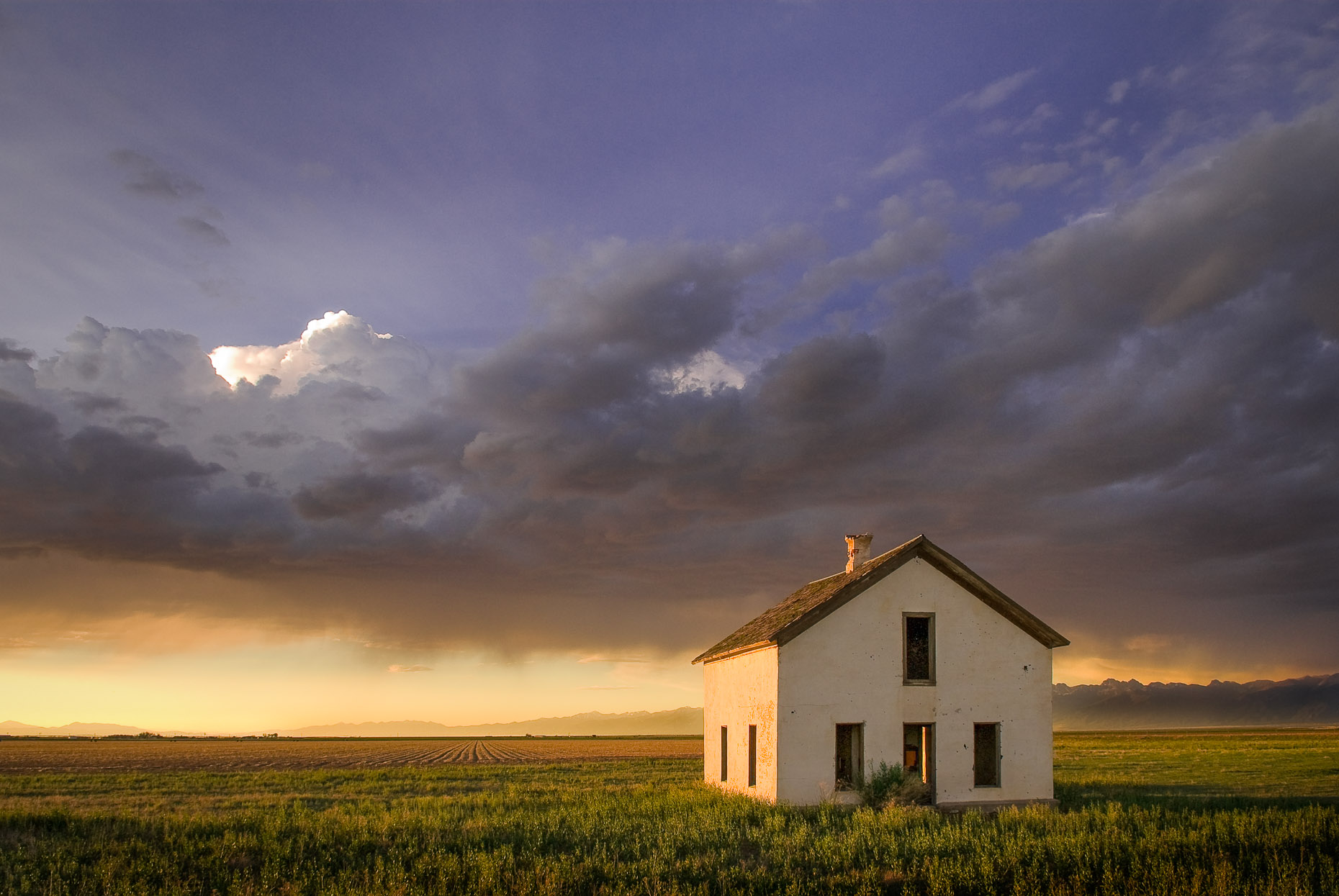 Abandoned small farm house in green field at dramatic sunset and rain storm.